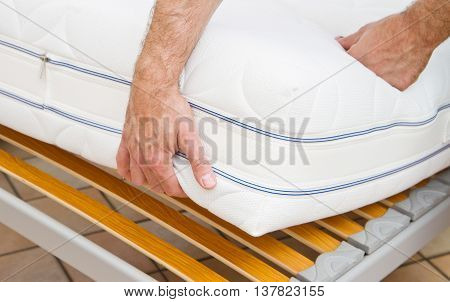 a man demonstrating the quality of mattress