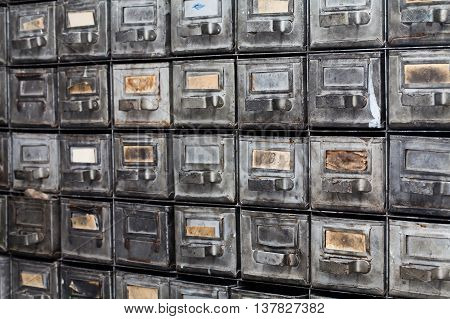 Metal drawers. Closed archive storage, filing cabinet interior. aged silver metallic boxes with index cards. library service information management.