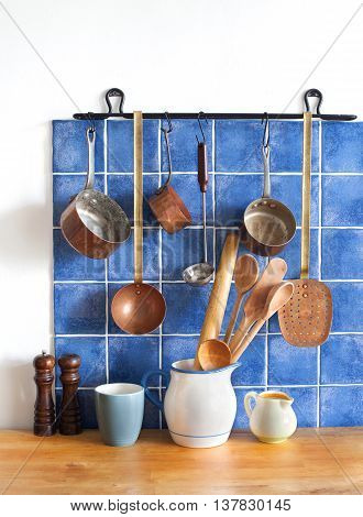 Retro design kitchen interior with accessories. Hanging copper kitchenware set. Pot, stewpot, spoon, skimmer, ladle. Different sizes pitchers, cup. wooden table. Blue tiles