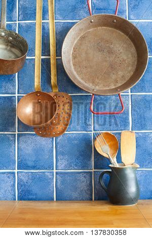 Vintage style kitchen accessories. Old utensils pan ladle pitcher with spoon, spatula. Wooden table and blue tile background. Kitchen interior