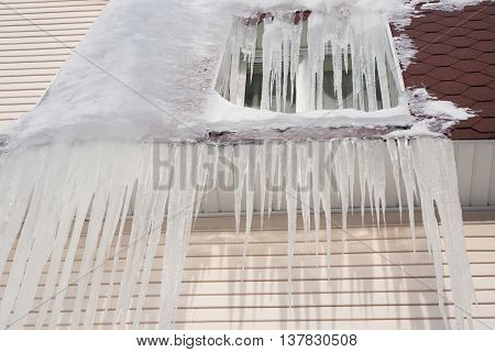 Frozen window. Icicles downspout on the brown roof. Cold weather conceptual image