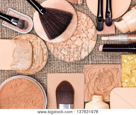 Makeup products to create the perfect complexion. Liquid and cream-to-powder foundation, concealers, compact, loose and shimmer golden powder, brushes and cosmetic sponges on sackcloth