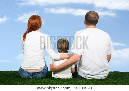 Rear view of family sitting together and looking at sky