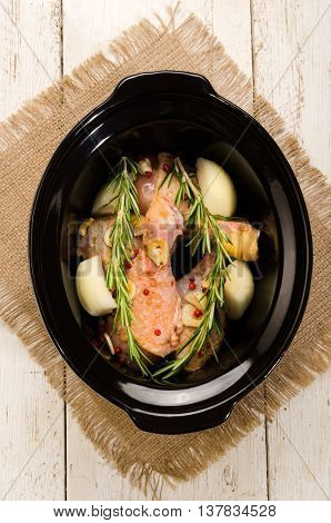 marinated chicken drumstick with red peppers onion garlic and rosemary in a black slow cooker