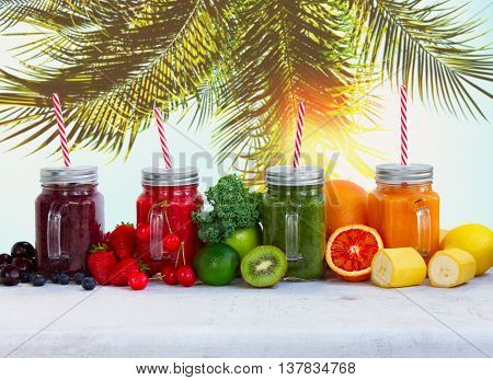 Smoothy drinks in glass jars with ingredients on white table under plam tree