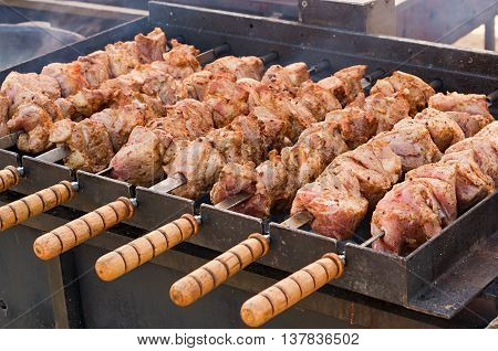 skewers of pork on skewers with wooden handles