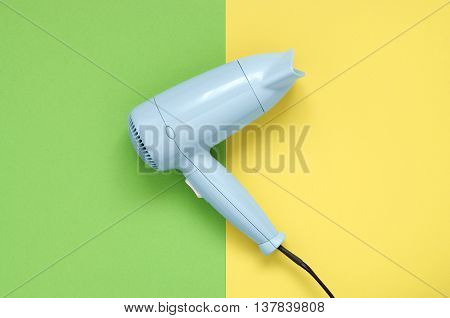 Blue hair dryer on green and yellow paper background