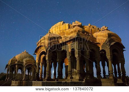 The royal cenotaphs of historic rulers, also known as Jaisalmer Chhatris, at Bada Bagh in Jaisalmer, Rajasthan, India. Night shot of ruins with stars