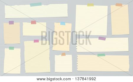 Pieces of light brown ruled torn note paper with colorful adhesive, sticky tape are stuck on background.