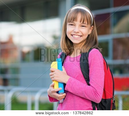 Outdoor portrait of happy girl 10-11 year old with book and backpack. Back to school concept.