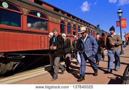 Strasburg Pennsylvania - October 16 2015: A Mennonite family the women wearing traditional white caps walking along the platform at the Strasburg Railroad