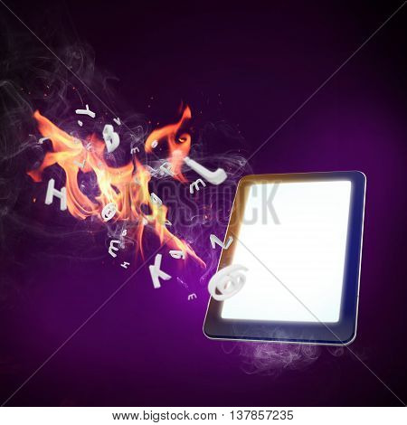 Close up of tablet computer burning in fire flames
