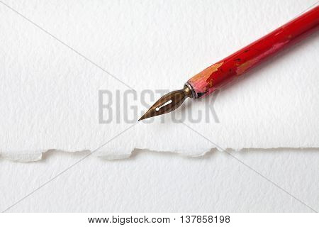 Red nib pen on white paper textured background. macro view fountain pen shallow depth of field