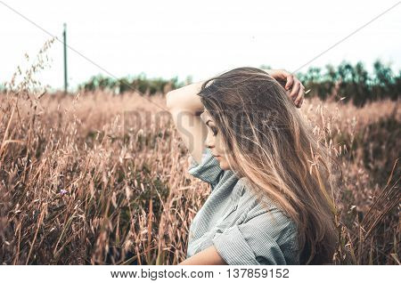 Beautiful and young girl in a man's shirt standing in the field. shirt for the girl. Nature. Wind inflates hair.