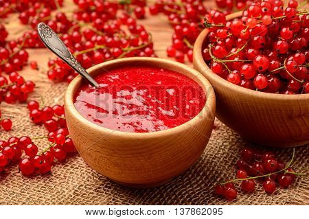 Red currants jam in wooden bowl .