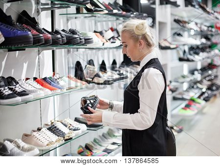 Shopping in the mall - woman choosing a pair of boots