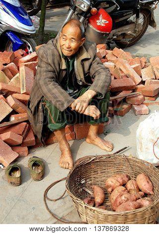 Huang Long Xi China - November 7 2007: Barefoot Chinese man seated on a pile of bricks selling sweet potatoes