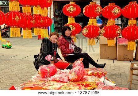 Jun Le China - February 3 2013: Two women sitting outside selling decorations for the Chinese Lunar New Year holiday