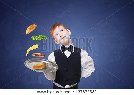 Little waiter dreaming with tray, serving hamburger. Cheeseburger levitates with separated toppings. Flying burger layers. Smiling redhead child boy in suit play restaurant servant at blue background