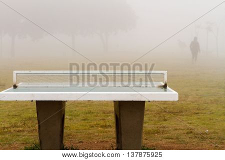 Table tennis in the fog with a silhouette in the background