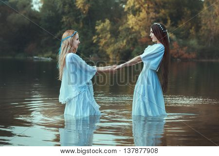 Two women holding hands they are dressed in white dresses and are in the water.