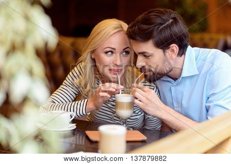 Pretty man and woman drinking latte from one cup with joy. They are looking at each other and smiling. Lovers are sitting at table in restaurant