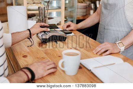 Modern paying system. Cropped image of man paying with NFC technology on mobile phone being in cafe