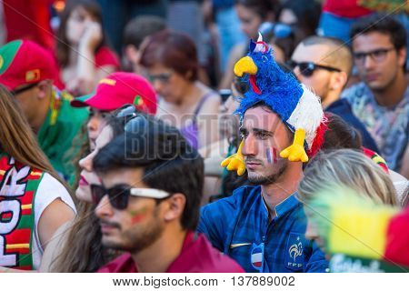 PORTO, PORTUGAL - JUL 10, 2016: French fan during video translation of the football match Portugal - France final of the European championship 2016, in Liberdade Square at city center of Porto.