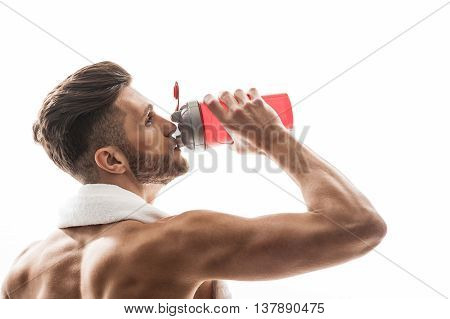 Cheerful young man is drinking water from sporty bottle. He is standing with relaxation. Athlete is holding towel over neck. Isolated