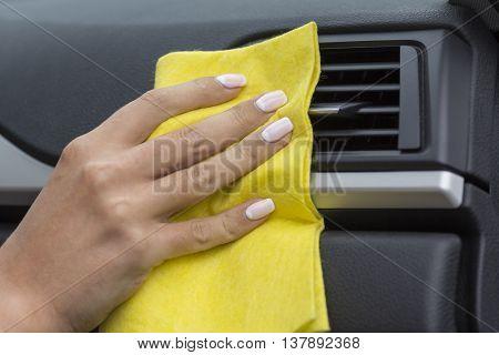 Hands girls wipe yellow cloth car interiors.