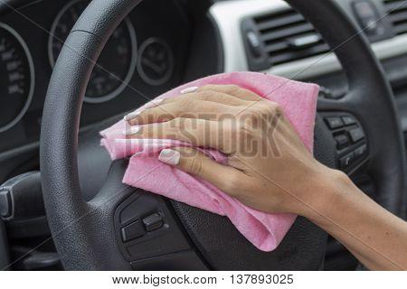 Hands girls wipe cloth wheel inside the vehicle.