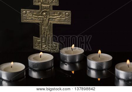 Lit Tea Candles and reflections with Crucifix with dark Background