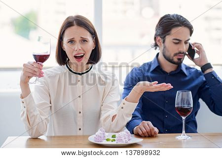 I am shoked. Young woman is bored while her husband is talking on mobile phone seriously. She is looking at camera with frustration. Lady is sitting and drinking wine
