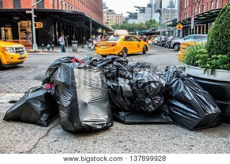 Black bags of trash on sidewalk in New York City street waiting for service trash truck. Garbage packed in big trash bags ready for transportation.