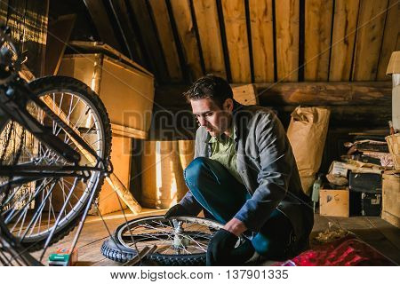 Young man repairs the bicycle in garage.