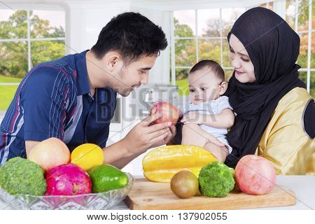 Portrait of young father with his wife giving a fresh apple fruit to little son in the kitchen