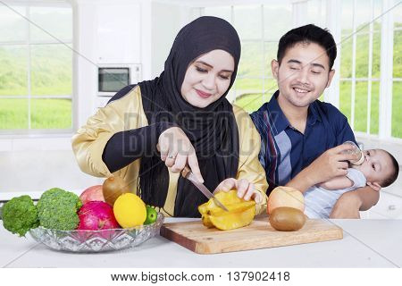 Happy middle eastern family preparing healthy superfood with fruit ingredients in the kitchen
