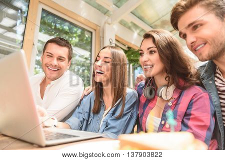 Checking their social networking profiles. Close up of group smiling friends hanging out in coffee shop with laptop amongst them