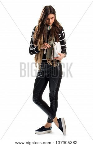 Girl touches white clutch bag. Sweatshirt and beige scarf. Trendy slip on shoes. Leather pants with side inserts.