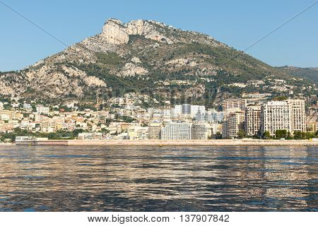 Luxury homes on the rocky Mediterranean coast of the French Riviera at Monte Carlo in Monaco, with mountain in the background. Horizontal with copy space for text