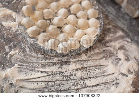 Raw homemade russian food - dumpling. They are in flour and have traditional form. Placed on the plate. Pork chicken mincemeat. Background table in kitchen.