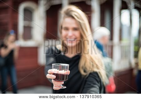 Happy woman drinking alcohol outoors on the party event. Focus on wine glass