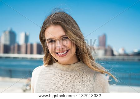 Close-up portrait of beautiful young woman with perfect natural white teeth smile at sunny day