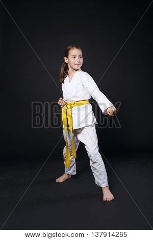 Little girl in karate suit kimono in studio at black background. Female child shows judo or karate stans in white uniform with yellow belt. Individual martial art sport for kids. Full body portrait