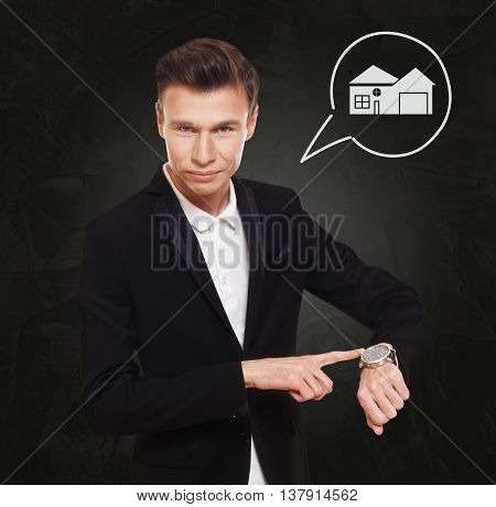 Time is money. Businessman point at his watch showing hand clock, real estate buying concept. Man in suit at black background, thinking cloud with house. Rent, lease, sell property.