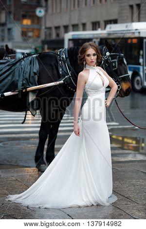 Portrait of beautiful woman bride in long white wedding dress posing in New York City street