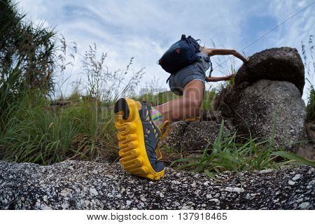 Lady hiker passing rocky terrain. Focus on the foot