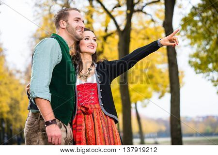 Happy woman and man in Tracht having a walk, girl pointing at something