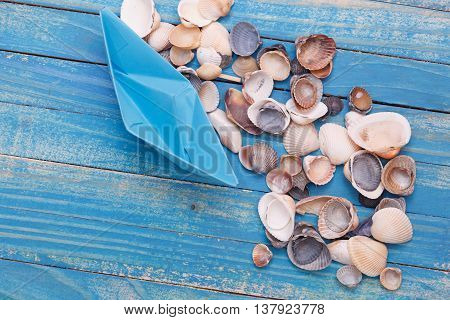 Blue paper Boat with shells. Travel Photo concept