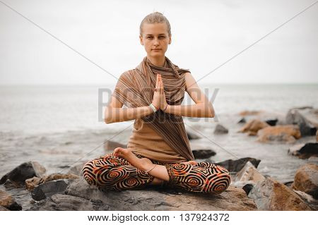 Woman meditating at the beach . yoga retreat. namaste in a lotus pose